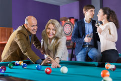 Group of cheerful charming positive friends playing billiards. And smiling in night club Stock Image
