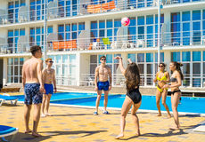 Group of cheerful couples friends playing volleyball. Party at smimming pool. Group of cheerful couples friends playing volleyball. Happy youth time Stock Photography