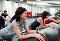 Group of cheerful female seniors in gym doing exercise on fit balls. stock photos