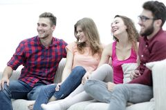 Group of cheerful friends sitting on the couch Stock Photo