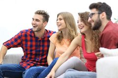 Group of cheerful friends sitting on the couch. In the living room stock photography