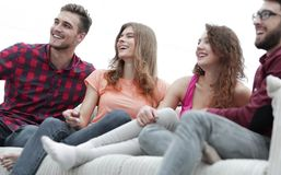 Group of cheerful friends sitting on the couch. In the living room royalty free stock photo