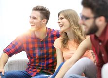 Group of cheerful friends sitting on the couch. In the living room royalty free stock photography