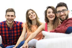 Group of cheerful friends sitting on sofa Royalty Free Stock Image