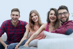 Group of cheerful friends sitting on sofa. And looking at camera stock image