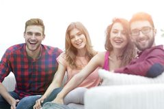Group of cheerful friends sitting on sofa. And looking at camera royalty free stock photos