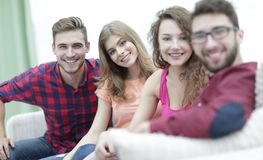 Group of cheerful friends sitting on sofa. And looking at camera royalty free stock photography