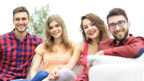 Group of cheerful friends sitting on sofa. And looking at camera royalty free stock image
