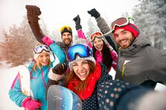 Group of cheerful friends with ski on winter holidays - Skiers h. Aving fun on the snow and making selfie Royalty Free Stock Photo