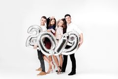 Group of cheerful friends of two girls and two guys dressed in stylish clothes are holding balloons in the shape of. Numbers 2019 on a white background in the royalty free stock images