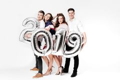 Group of cheerful friends of two girls and two guys dressed in stylish clothes are holding balloons in the shape of. Numbers 2019 on a white background in the stock photos