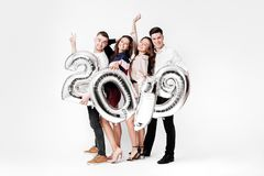 Group of cheerful friends of two girls and two guys dressed in stylish clothes are holding balloons in the shape of. Numbers 2019 on a white background in the stock image