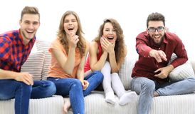 Group of cheerful friends watching their favorite movie. Sitting on the couch royalty free stock photo