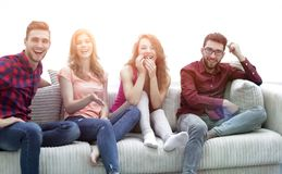 Group of cheerful friends watching their favorite movie. Sitting on the couch stock photo