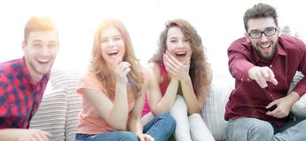 Group of cheerful friends watching their favorite movie. Sitting on the couch stock image