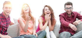Group of cheerful friends watching their favorite movie. Sitting on the couch stock photos
