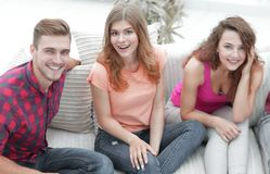 Group of cheerful friends watching videos, sitting on the couch. In the living room stock photography