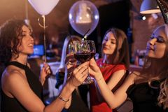 Group of cheerful girls having a party standing clinking glasses together at night club stock photos