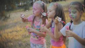 Group of cheerful girls in the yard playing with soap bubbles