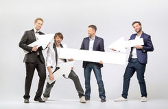Group of cheerful guys with arrows and boards Stock Photo