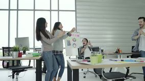 Group of cheerful happy Asian creative business women and men enjoy and having fun dancing while working in her office. stock footage