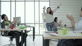 Group of cheerful happy Asian creative business women and men enjoy and having fun dancing while working in her office. stock video footage