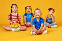 Group of cheerful happy children on colored yellow background. Group of cheerful happy children on a colored yellow background stock image