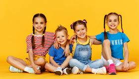Group of cheerful happy children on colored yellow background royalty free stock images