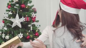 Group of cheerful happy young Asian women giving christmas gifts to each other in her living room at home in Christmas Festival. stock video footage