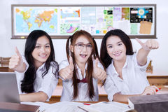 Group of cheerful learners showing thumbs up Stock Photo