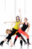 Group of cheerful modern dancer females. Group of three cheerful sporty young women doing aerobics exercises, modern dance movements in class. Active, healthy royalty free stock photo