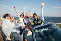 Group of cheerful people driving and having fun in cabriolet Stock Images