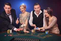 Group of a stylish rich friends are playing poker at casino. stock images