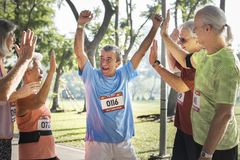 Group of cheerful senior runners at the park stock photo