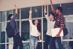 Group of cheerful students with raised hands in the campus, Stu royalty free stock photography
