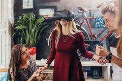 Group of cheerful students supporting their female friend playing funny game using virtual reality helmet in living room.  Stock Images