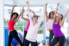 Group of cheerful women exercising with arms raised Royalty Free Stock Photos