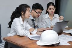 Group of cheerful young Asian business people working together on a laptop computer at office. Teamwork brainstroming concept. Sel. Ective focus and shallow Royalty Free Stock Images