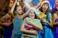 Group of cheerful young girls celebrating Christmas. Gifts Royalty Free Stock Photo