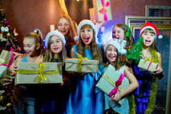 Group of cheerful young girls celebrating Christmas. Gifts Stock Images