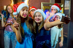 Group of cheerful young girls celebrating Christmas. Selfie. Group of cheerful young girls celebrating Christmas near the Christmas tree with lights. Selfie Royalty Free Stock Photo
