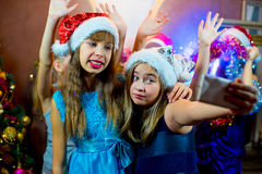 Group of cheerful young girls celebrating Christmas. Selfie. Group of cheerful young girls celebrating Christmas near the Christmas tree with lights. Selfie Stock Photography