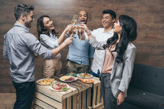 Group of cheerful young people clinking champagne glasses above festive table royalty free stock images