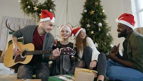 A group of cheerful young people having fun at home near a Christmas tree, one of the guys playing guitar