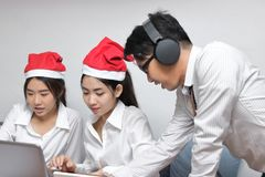 Group of cheerful young people with Santa hats shopping online with laptop in living room at home. Merry Christmas and happy holid stock photos