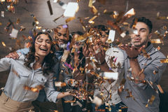 Group of cheerful young people standing together and celebrating with confetti. Multiethnic group of cheerful young people standing together and celebrating with Stock Image