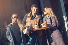 Group of cheerful young people talking, drinking coffee and eating croissant in cafe outdoor on sunny day. Concept togetherness, Royalty Free Stock Image