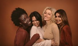 Group of cheerful young women standing together. On brown background. Multi ethnic female friends in studio Royalty Free Stock Images