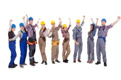 Group of cheering artisans. Large group of diverse multiethnic cheering artisans in dungarees and hardhats with toolbelt standing in a line isolated on white Stock Image
