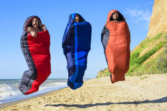 Group of cheering hikers jumping in a sleeping bags on the seaside. Three young caucasian males in sleeping bags on the beach royalty free stock photography